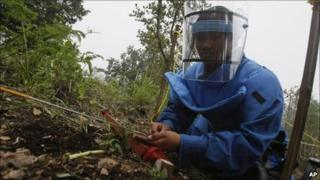 A Nepalese female soldier clears an anti-personnel landmine at Phulchoki on 14 July 2011