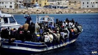 Italian police escort a boat carrying migrants from Libya into Lampedusa, 9 April