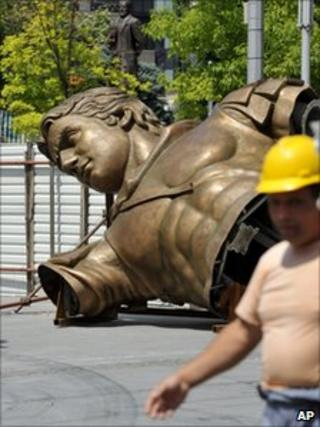 A construction worker passes the trunk of the Alexander statue in Macedonia's capital Skopje, 14 June
