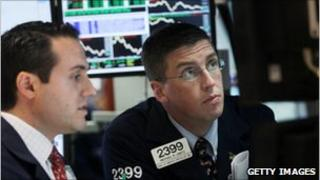 Two traders look at price screens