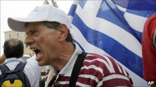 Demonstrator shouts slogans outside the parliament in central Athens