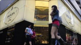 Pedestrians walk past a Prada shop in Hong Kong