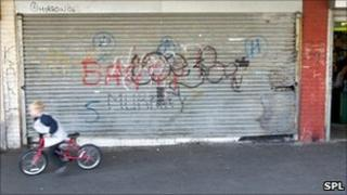 A child rides past a closed shop on a bicycle