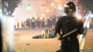 Couple between police and rioters in Vancouver, Canada (16 June 2011)