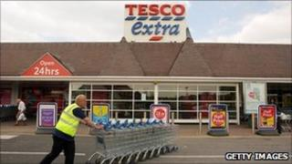 Tesco employee pushes trolleys in front of a branch