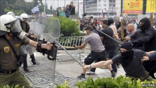 Masked demonstrators and riot police clash near the Greek parliament in Athens on 15 June 2011