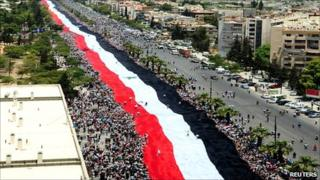 Pro-government protesters carry a large Syrian flag along the al-Mezzeh highway in Damascus on 15 June 2011