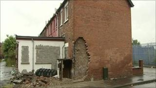 House with bricks removed from gable wall