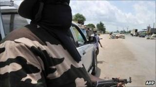 An armed masked militiaman stands at a makeshift checkpoint in Abidjan