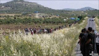 Turkish police watch as Syrians cross the border seeking safety. 15 June 2011
