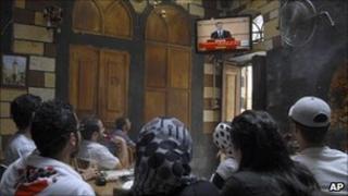 Syrian citizens watch President Assad's speech in a Damascus cafe, 20 June