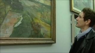Paul McGann looking at an Albert Richards paintings