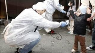 Officials in protective gear check for signs of radiation on children who are from the evacuation area near the Fukushima Daiichi nuclear plant in Koriyama