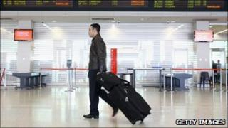 A passenger walks past the departure screen as airlines cancel flights due to volcanic ash at Melbourne Airport