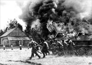 German soldiers, backed by armoured personnel carriers, move into a burning village somewhere along the German-Soviet front, 26 June 1941