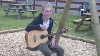 Lewis Mokler sitting on a swing, holding his guitar
