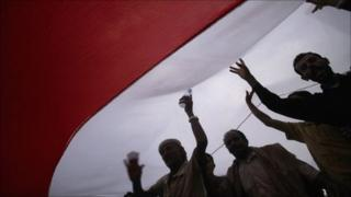 Anti-government protesters shout slogans under a Yemeni national flag during a demonstration against President Ali Abdullah Saleh in Sanaa, 21 June 2011