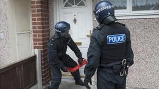 Police officers raiding house on Merseyside