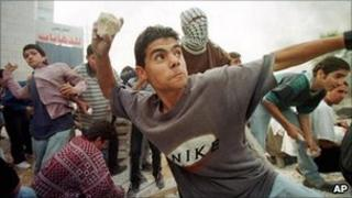 A Palestinian youth pelts Israeli soldiers with stones during clashes outside the West Bank town of Ramallah in Dec 1998.