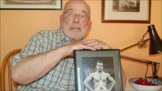 Ray Myland with a picture of himself at the 1952 Helsinki Olympics