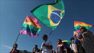 People wave Gay movement flags, left and right, and a Brazilian one, centre, during a march against homophobia in Brasilia, Brazil, Wednesday, 18 May 2011
