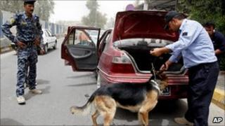 An Iraqi policeman uses a dog to search a car at a checkpoint in Baghdad, Iraq, 23 June 2011