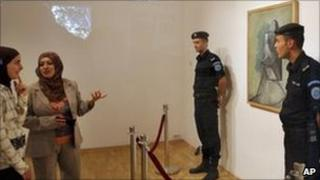 Palestinian women look at Picasso's Buste De Femme painting in Ramallah