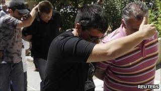 Plainclothes policemen escort two civilians arrested in connection with a probe into match-fixing in Greek football in Athens on Thursday