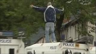 Man standing on police vehicle