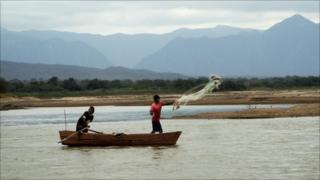 Fishermen throw a net out over the Pilcomayo River