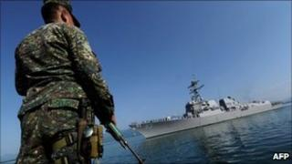 A Philippine naval personnel stands on guard during the arrival of missile destroyer USS Chung Hoon in Palawan