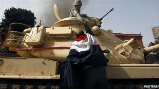 A protester wearing an Egyptian flag shakes hands with a soldier in a tank, Cairo, Jan 2011