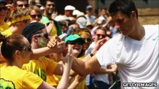 Bernard Tomic shakes hands with fans after winning his fourth round match against Xavier Malisse on June 27, 2011