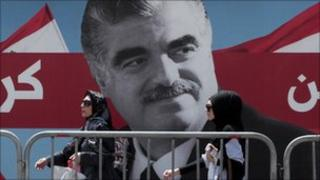 Women pass by a giant portrait of former Lebanese Prime Minister Rafik Hariri near his grave, Beirut, Lebanon, 30 June 2011