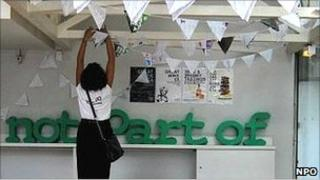 A woman hangs bunting at Not Part Of