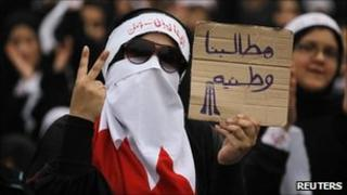 "A Bahraini Shia protester holds up a placard reading: ""Our demands are for country"" (1 July 2011)"
