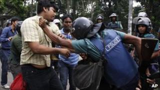 A Bangladeshi riot policeman detains an activist during a six-hour general strike in Dhaka.