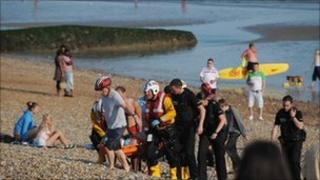 Rescuers carry the man from the sea