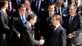 Russian President Dmitry Medvedev (bottom R) and NATO chief Anders Fogh Rasmussen (L) shake hands as they pose for a photo with the participants in the Russia-Nato Council in the Black Sea resort of Sochi, on Monday