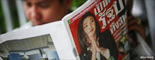 A man reads a newspaper with a cover photo of Yingluck Shinawatra in Bangkok (4 July)