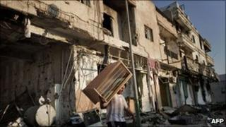 A Libyan youth carries away a piece of furniture from a destroyed building in Tripoli street