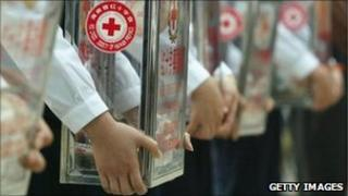 Workers of the Hainan Red Cross hold collection boxes during a fundraising event for tsunami relief on January 11, 2005 in Haikou, China