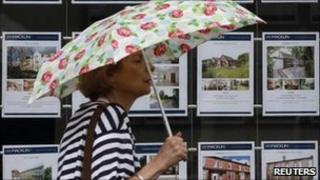 lady walks past estate agent