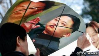North Korean defectors hold defaced posters of North Korea leader Kim Jong-il and his son Kim Jong-un as they participate in a anti-North Korea protest in South Korea