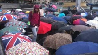 Umbrellas go up in another downpour in Trafalgar Square