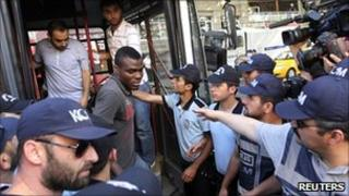 Emmanuel Emenike, Fenerbahce striker, is surrounded by policemen as he arrives at court in Istanbul on 6 July