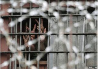 Detainees make victory salutes from behind the bars of a detention centre in Minsk, 6 July