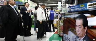 People watch live TV broadcasting in a Tokyo discount store from the Diet as Japanese Prime Minister Naoto Kan reacts after he survived a no-confidence motion during Lower House plenary session Thursday, June 2, 2011
