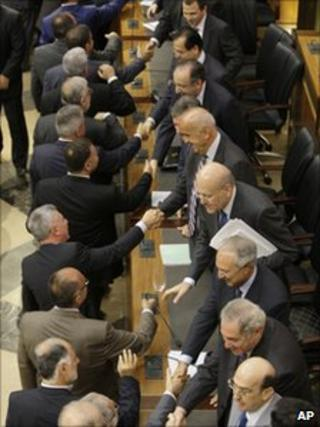 MPs, left, congratulate ministers at the parliament in Beirut, 7 July