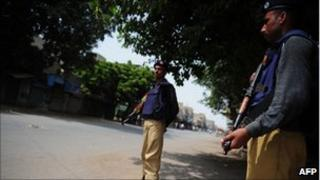 Pakistani policemen stand guard in a deserted street in a western neighbourhood affected by the political violence in Karachi on July 7, 2011